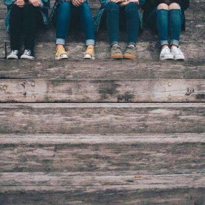 Four people sit at the top of a set of stairs